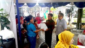 Lurah Petamburan Parsiyo saat menyerahkan Bantuan Pangan Non Tunai kepada salah satu warga disaksikan Branch Manager Bank BNI Kantor Cabang Senayan, Yong Hanafi